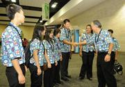 Retired Bank of Hawaii employee Randall Matsumoto, right, greets Hanlin Cui, a junior at McKinley High School, with other students from the school's Academy of Finance class at the Hawaii Convention Center.