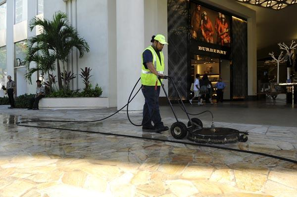 Atapana Muagututia cleans the new sidewalk in front of the DFS Waikiki Galleria in Waikiki. New sidewalks were part of the City and County of Honolulu's preparations for the Asia-Pacific Economic Cooperation Leaders' Week meetings.