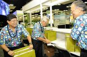 Bank of Hawaii retirees and APEC volunteers, from left, Vernon Miyake, Werner Umbhau and Randall Matsumoto distribute Hawaii-made gifts to the media.