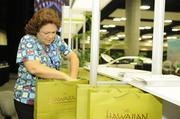 APEC volunteer and retired Bank of Hawaii employee Victoria Ward prepares gift bags for members of the media.