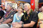 "University of Hawaii head football coach Norm Chow and his wife, Diane, listen to Gov. Neil Abercrombie as he speaks to ""Chow Time"" goers at the Downtown Athletic Club."