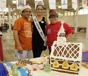Easter Seals supporter Barend Bacon, left, and son Daniel Bacon, an Easter Seals participant, pose with Miss Hawaii USA 2013 Brianna Acosta at the 13th-annual Easter Seals Hawaii Gingerbread Family Festival at the Blaisdell Center in early December.