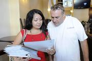 Lori Lamug, left, implementation consultant for Pro Service Hawaii, reviews human resource documents with Danny Dolan prior to the reopening of Ferguson's Irish Pub in downtown Honolulu.