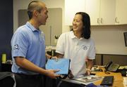 Stanley Lau, left, CEO of Hawaii Tech Support, and Marketing Director Belinda Lau look at marketing materials and promotional items for the company.