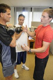 Trainer Trevor Spring shows Kevin Gooding, left, and Josh Miyagishima, right, how to use a kettlebell at Oceanit's Honolulu office. Oceanit was the winner among medium-sized businesses for Pacific Business News' Healthiest Employers.