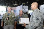"""Hawaii Army National Guardsman Wilson Utu, right, inquires about federal jobopportunities with Henry Keanini Jr., left, Code 930 Operations General Foreman for Pearl Harbor Naval Shipyard and Robert Perreira, center, branch head for shop 38, Pearl Harbor Naval Shipyard on Monday at the """"Hiring our Heroes"""" job fair for veterans and military spouses  sponsored by the U.S. Chamber of Commerce at Joint Base Pearl Harbor-Hickam near Pearl Harbor, Hawaii."""
