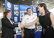 """Military spouse Teresa Joseph, right, talks with Renee Awana, left, of the human resources department at Navy Region Hawaii, and Ryan Yoshimoto, battalion chief for the Federal Fire Department, about employment opportunities on Monday at the """"Hiring our Heroes"""" job fair for veterans and military spouses sponsored by the U.S. Chamber of Commerce at Joint Base Pearl Harbor-Hickam near Pearl Harbor, Hawaii."""