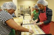 From left, Nelda Fernandez, Maria Teresa Caronan and Conchita Bumanglag hand-place pineapple in each pineapple shortbread cookie at Honolulu Cookie Co.'s new facility on Sand Island Access Road in Honolulu.