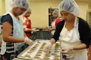 Michelle Anchetta, left, and Jenny Grace Visitacion hand-place a coffee bean in Kona coffee shortbread cookies at Honolulu Cookie Co.'s new facility on Sand Island Access Road in Honolulu.