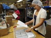 Wendy Cabrera, shipping clerk, prepares a special order for mailing from online sales at Honolulu Cookie Co.'s new facility on Sand Island Access Road in Honolulu.