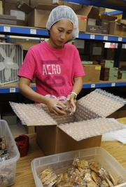 Vilma Ceredon, shipping lead, prepares a mail order at Honolulu Cookie Co.'s new facility on Sand Island Access Road in Honolulu.