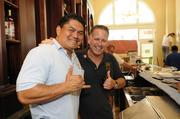 Gabby Lucas, Oceanic Time Warner business class service and installation, throws a shaka with J.J. Niebuhr, right, co-owner of Ferguson's Irish Pub in downtown Honolulu.