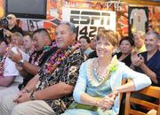 Keith Uperesa, offensive assistant coach, and Diane Chow listen to University of Hawaii head football coach Norm Chow introduce his new staff.
