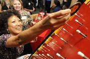 """Sunny-Aloha Miller plays """"plinko"""" at the Crown Relocations booth."""
