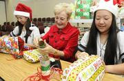 Sacred Hearts Academy Head of School Betty White, center, and seniors Kristen Pang, left, and Kristen Nishimoto, wrap donated items for adopted families in transitional shelters for the Loliana Hale project. Sacred Hearts Academy has participated in the program for 22 years.