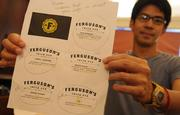 Scott Naauao, senior designer at Wall-to-Wall Studios, shows the proofs of the business card layouts for the partners of Ferguson's Irish Pub in downtown Honolulu.