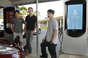 Volta Industries owners, from left, Chris Ching, director of operations; Michael Menendez, lead engineer; and CEO Scott Mercer stand near their two charging stations — one of which displays as ad for Hawaii solar contractor RevoluSun — at Kahala Mall in Honolulu. Their business model is simple: Make the charging stations available free of charge at select locations, then charge businesses to attach their advertising messages to the stations.