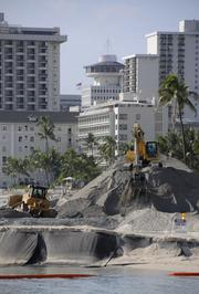 Crews work to distribute sand as part of a project to replenish Hawaii's famed Waikiki Beach. The sand placement is expected to be complete on April 14.
