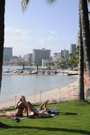 Sunbathers lounge near a construction fence blocking beachgoers from Hawaii's Waikiki Beach during the sand-replenishment project. The state says the sand placement is scheduled to be finished on April 14.