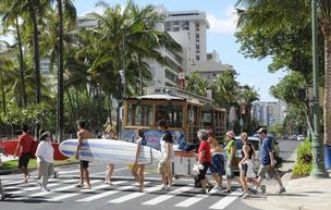 Pedestrians cross an intersection of Kalakaua Avenue in Waikiki with the Waikiki trolley in the background. The number of visitors to Hawaii in January rose 6 percent, while spending also rose 6 percent to $1.43 billion, according to the Hawaii Tourism Au