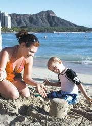 Minnesota visitor Erin Hayes helps her son Kiran, 3, build a castle. This particular area, in front of the Royal Hawaiian Hotel, is part of where the state has plans to replenish sand so the beach will return to its 1985 width.