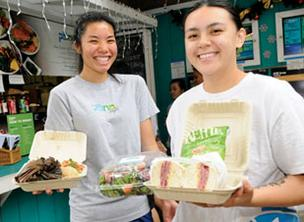 Shantay Sueoka (left), manager of the Koko Marina location, holds a Hawaiian Plate, which features laulau, lomi lomi salmon, and Paina Café's famous spicy tuna poke. Joe Matusiak, manager of the Ward location, holds the berry berry good salad and pastrami sandwich served reuben style with sauerkraut and Thousand Island dressing.