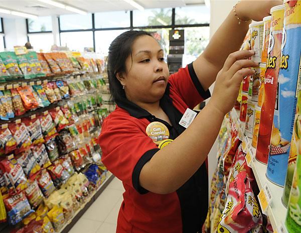 Sales associate Clariechel Vinluan stocks the shelves at the 7-Eleven store on Nimitz Highway. The convenience store chain plans to have 100 stores in Hawaii within four years.