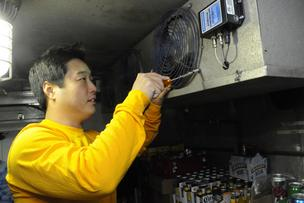 Ryan Kohatsu, an energy-efficiency engineer for Energy Industries, installs new energy-efficient refrigeration at a 7-Eleven store on Nuuanu Avenue.