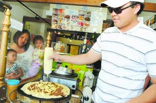 Aloha Crepes and Aloha Snow Flakes co-owner Garret Chang makes a 'Banana Jamma' for customer Lah Tarrant, who is holding Anna Phengde, 2, and Zahara Tarrant, 18 months. Chang and his business partners, Rick and Mark Monroe, opened the shop at 3620 Waialae Ave. in Kaimuki in February. All three are Kaimuki residents. 'Kaimuki is such a food destination so we wanted to be in the middle of all of that, too,' Chang says. The Kaimuki shop is the second location for Aloha Crepes and Aloha Snow Flakes, which opened in Waimalu about 18 months ago.