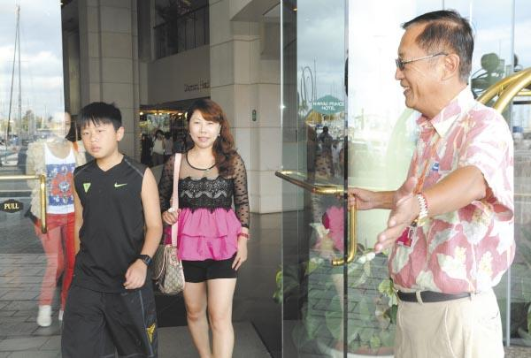 Peter Cheng, right, with Galaxy Tours assists Chinese visitors staying at the Hawaii Prince Hotel. Yang Guo, center, and her son, Gang, and daughter Liu Yan, far left, were in Hawaii for the first time. The number of Chinese visitors in Hawaii will grow 40 percent in 2012.