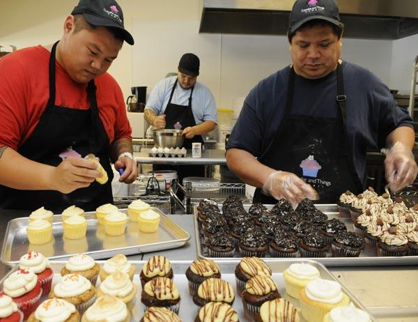 Herbert DeAguira, right, owner of Cupcake and Things Hawaii, arranges cookies n' cream cupcakes while his son-in-law, Michael Saito, left, adds sugar sprinkles to lilikoi cupcakes and his other son-in-law, Kenji Saito, mixes a new batch. DeAguira says a key to running his three-month-old business at 885 Kamokila Blvd. in Kapolei, is defining what a cupcake is. Toward that goal, he offers 29 varieties, including a classic cupcake with no filling for $2.49 and a cupcake with cream cheese icing for $2.99.