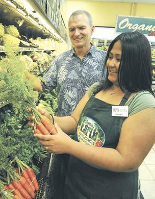 Claudine Cabison, manager of Down to Earth in Kailua, stocks up on organic produce as CEO Mark Fergusson looks on.