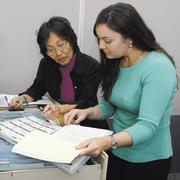 Nancy Hashimoto, left, human resources manager for EMSS, checks personnel files with Kim Watanabe, administrative manager.