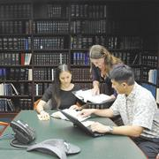 Goodsill Anderson Quinn & Stifel associates, from left, Claire Goldberg, Abby Holden and Will Tanaka research municipal corporations in their firm's library.