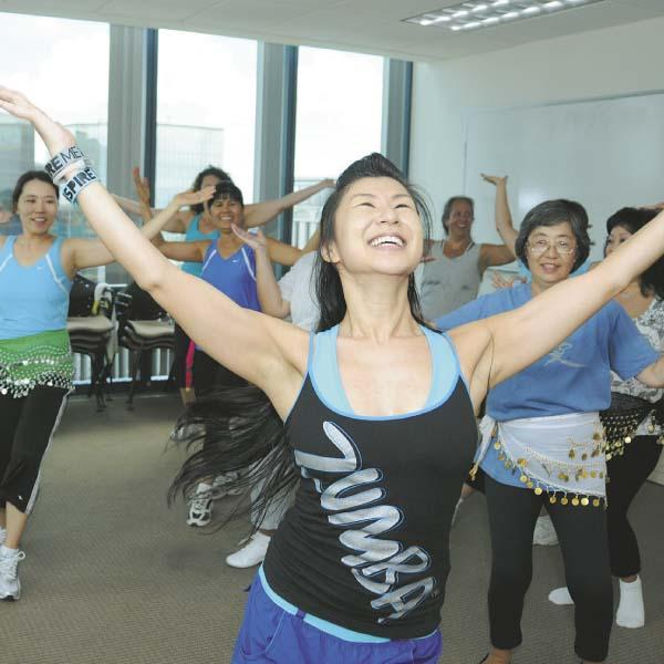 HPH statistician and researcher Chieko Kimata leads a Zumba class for fellow employees. The health-care provider subsidizes the cost of many wellness and fitness programs for its employees.