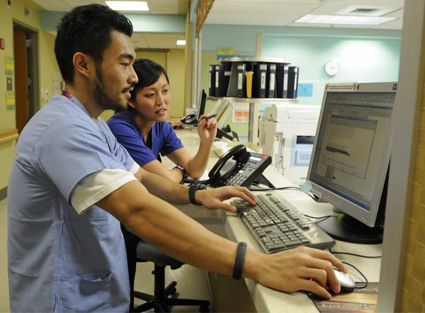 Registered nurse Justin Lozano and nursing assistant Kelsi Hasegawa chart patient health-care needs at The Queen's Medical Center. Health-care officials say lawmakers will be deciding on several key issues in 2013.