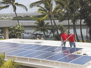Hoku Solar employees Chaston Kaapa, left, and Koa Kaapa, complete the final touches on a photovoltaic installation for the offices of the USS Bowfin Museum. Despite having plenty of work, Hoku Solar faces an uncertain future.