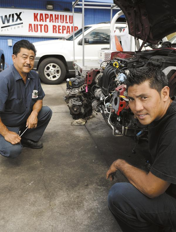 Kapahulu Auto Repair co-owners Ernest Moriwake, left, and Michael Sonoda replace the engine on a 2004 Mini Cooper.