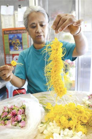 Nita Galario makes a yellow ohaialii lei that will be worn by a dancer in this weekend's Merrie Monarch Hula Festival in Hilo. The owner of Lita's Leis & Flower Shoppe at 59 N. Beretania St. had a busy week, preparing specialty lei for halau gathering on