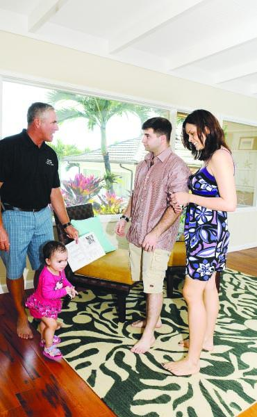 David Kucic, left, owner of Hawaii Military Realty Inc., shows a single-family home listing in Kaneohe to Mike and Maddison Vaccaro and their 18-month-old daughter, Miranda. Mike Vaccaro is on active duty with the Navy and the family is currently renting.