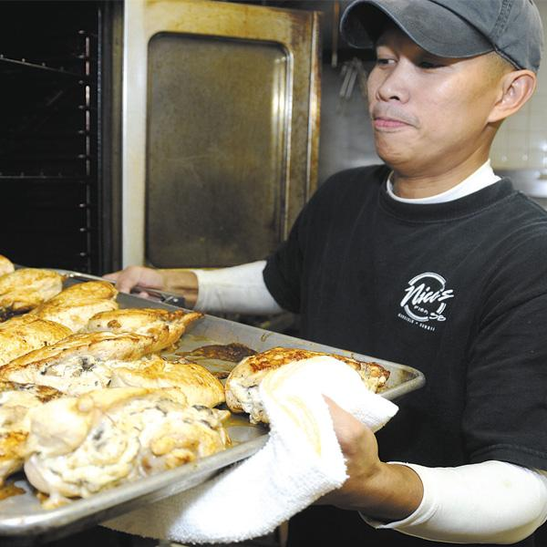 Jeorge Siores, head chef for Nico's at Pier 38, prepares the day's special — baked shiitake mushroom cream cheese-stuffed chicken breast with hollandaise sauce. The popular Honolulu eatery prepares local dishes with a European flair. Owner Nico Chaize says they sell approximately 700 lunches a day with Fridays being their busiest days.