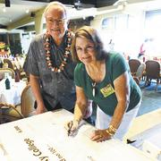 The Lani-Kailua Outdoor Circle has awarded $6,000 to fund scholarships for students in environmental studies at Windward Community College. Lani-Kailua Outdoor Circle President Lyn Turner signs the ceremonial check as Windward Community College Chancellor Doug Dykstra looks on.