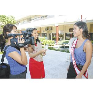 PacRim Marketing Group videographer Kiku Byrne, left, and producer Saiko Nozaki, center, videotape newly crowned Miss Chinatown Hawaii Nicole Leong in the Chinese Cultural Plaza.