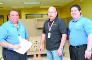 From left, Pelatron President and COO Harvey Kim, Principal Engineer Elmer Looney and VP of Engineering and Technology Bronson Aken stand in front of part of the Network on the Move hardware being worked on from their offices near Honolulu International Airport.