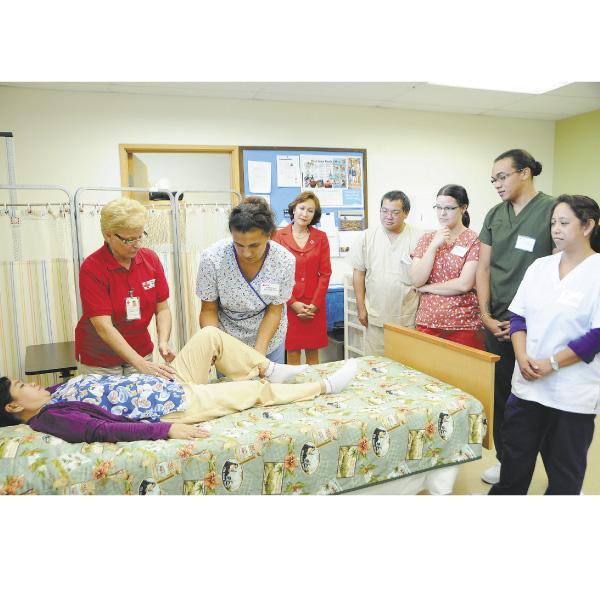 Instructor Terry Price, left,  works with Kathy Ann Keawe on Elizabeth Pinzon (lying down) during a Red Cross training class to become certified nurse aides.Watching, from left, are CEO Coralie Chun Matayoshi, Chris Yonashiro, Danielle Fisher, Cory Napoleon and Imelda Ildefonso.