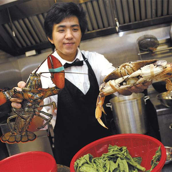 Peng Gong, assistant manager for the Canton Seafood Restaurant, shows the new restaurant's fresh catch, a live one-pound fresh Maine lobster and a two-pound crab. The Canton Seafood Restaurant, which is owned by the same company that owns Chin's Chinatown Restaurant on Maunakea Street, opened April 10 at 923 Keeaumoku St. The building previously housed Di Ventus Dog Hotel & Spa and before that, Maui Divers Jewelry.