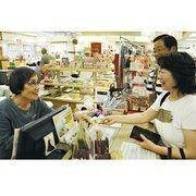 Shirokiya sales associate Fujiko Ogawa, left, gives a receipt and change to customers Hiroko Shimura, right, and her husband, Yoshiharu.