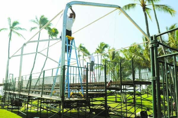 Giovani Roilan, an installer for Dolphin Event Services, attaches a cable to secure a tent for a skybox next to the 17th green at Waialae Country Club. Skybox sponsors will entertain guests over four days beginning next Thursday.