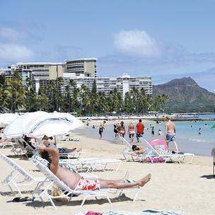 Visitors enjoy a warm, sunny day on Waikiki Beach this week. Tourism officials expect the beaches to be full this summer, despite fewer air seats to Hawaii, rising airfares and a decline in all-inclusive deals and packages.