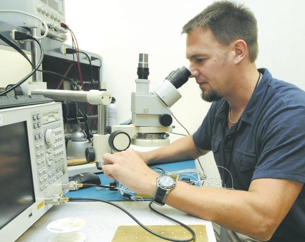 Craig Nevin, principal engineer for TeraSys Technologies, checks electrical performance at the company's downtown Honolulu laboratory. Until now, the five-year-old company has based its business model on U.S. Department of Defense contracts.
